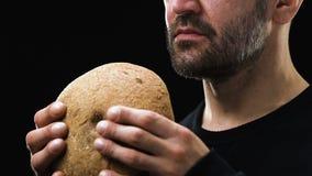Het hongerige gebaarde brood van de mensenholding, armoedeconcept, sociale onzekerheid, close-up stock videobeelden