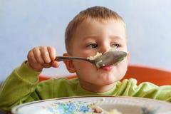 Het hongerige kind eet lunch met grote eetlust De leuke jongen eet deegwaren stock afbeelding