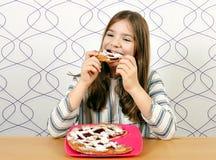 Het hongerige meisje eet een pastei royalty-vrije stock afbeelding