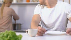 Het hongerige ongeduldige mes en de vork die van de echtgenootholding op maaltijd van langzame vrouw wachten stock videobeelden