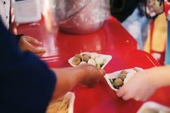 Het hongerprobleem van de armen: de dakloze mensen ontvangen voedsel en liefdadigheid stock fotografie