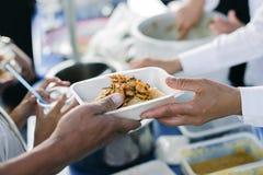 Het hongerprobleem van de armen: de dakloze mensen ontvangen voedsel en liefdadigheid royalty-vrije stock fotografie