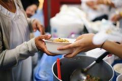 Het hongerprobleem van de armen: de dakloze mensen ontvangen voedsel en liefdadigheid stock afbeelding
