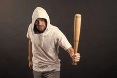 Het honkbalknuppel van de mensengreep, agressie De kap van de hooliganslijtage in hoody, manier De gangsterkerel dreigt met knupp royalty-vrije stock afbeelding