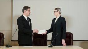 Het hoofd geeft de toekenning in envelop aan de werknemer voor het beste werk stock footage