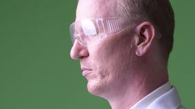 Het hoofd schoot profielmening van rijpe kale mens arts die beschermende glazen dragen stock videobeelden