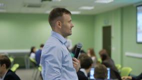 Het hoofd van bedrijfs opleidende student luistert vastbesloten aan de prestaties, kijkend presentatie, bespreekt en vraagt hen stock footage