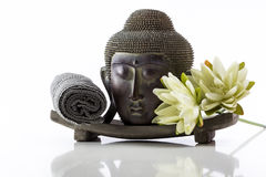 Het hoofd van Boedha op een witte achtergrond, een handdoek en een lotusbloem Stock Foto's