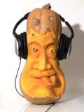 Het hoofd van de Haloweenpompoen met hoofdtelefoons wordt gebeeldhouwd die Royalty-vrije Stock Foto