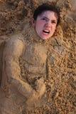 Het hoofd van de Preteenjongen in strandzand het gelukkige glimlachen Stock Foto's