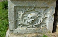 Het hoofd van de schedeldood op grafsteen stock fotografie