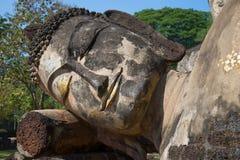 Het hoofd van doende leunen Boedha dicht omhoog op een zonnige middag Ruïnes van de oude Boeddhistische tempel van Wat Phra Kaeo  royalty-vrije stock foto's