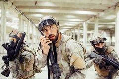 Het hoofd van militairen houdt geweer in handen en spreekt aan draagbare radio Hij kijkt omhoog aan de kant Andere twee kerels Stock Afbeelding