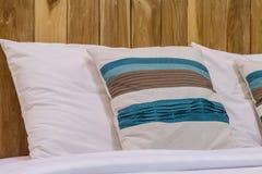Het hoofdkussen op bed met houten achtergrond Stock Foto