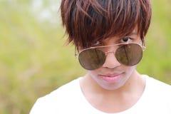 Het hoofdschot van Thaise mannelijke tiener in witte t-shirt en zonnebril staart bij camera stock foto's
