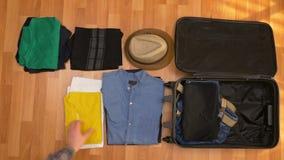 Het hoogste concept van de meningsreis de oppasser die van de toeristenmens zijn kleren inpakken in een koffer stock footage