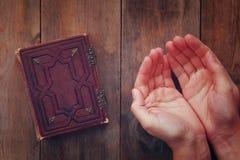 Het hoogste die meningsbeeld van bemant handen in gebed naast gebedboek worden gevouwen concept voor godsdienst, spiritualiteit e Stock Afbeelding