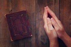 Het hoogste die meningsbeeld van bemant handen in gebed naast gebedboek worden gevouwen concept voor godsdienst, spiritualiteit e Stock Foto