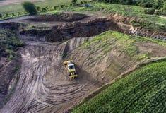 Het hoogste graafwerktuig die van de menings zware machine bagger in modder aan bouwwerf met het groene landschap omringen werken Royalty-vrije Stock Afbeeldingen