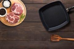 Het hoogste lapje vlees van de menings ruwe varkenskotelet, grillpan en spatel op de houten achtergrond stock afbeeldingen