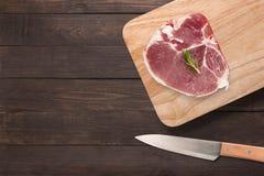 Het hoogste lapje vlees van de menings ruwe varkenskotelet op scherpe raad en mes op woode stock foto