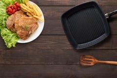 Het hoogste lapje vlees van de meningsvarkenskotelet, grillpan en spatel op de houten bedelaars stock afbeelding