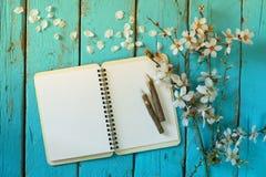 Het hoogste meningsbeeld van de lente witte kers komt boom, open leeg notitieboekje naast houten kleurrijke potloden op houten li Stock Foto's