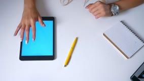 Het hoogste schot, kempt hand van vrouw typt op het blauwe scherm van haar tablet die op witte Desktop, bureaustemming legt stock footage
