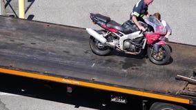 Het hoogste schot van motorfiets wordt ontladen van een flatbed vervoerder van de slepenvrachtwagen stock video