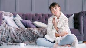 Het hoogtepunt schoot het leuke jonge vrouw proberen krijgend warm in witte pluizige plaidzitting op tapijt verpakt stock video