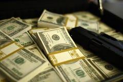 Het hoogtepunt van de aktentas van contant geld en pistool stock afbeelding