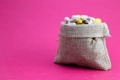 Het hoogtepunt van de jutezak van drug en geneeskundepillen Betaalde geneeskunde Aankoop van geneesmiddelen roze achtergrond Gene stock fotografie