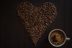 Het hoogtepunt van de koffiekop van koffie en geroosterde koffiebonen op houten lijst in de vorm van haard stock afbeelding