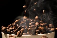 Het hoogtepunt van de koffiemok van koffiebonen met rook Stock Fotografie
