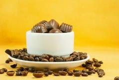 Het hoogtepunt van de kop met koffiebonen en chocoladesuikergoed stock foto