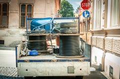 Het hoogtepunt van de ladingsvrachtwagen van hulpmiddelen en de ondergrondse optische die kabels rollen voor Internet op de straa royalty-vrije stock foto