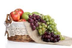 Het hoogtepunt van de mand van appelen en sappige druiven Stock Fotografie
