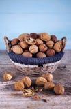 Het hoogtepunt van de okkernootmand van gehele noten in shells en gebroken wat Stock Foto