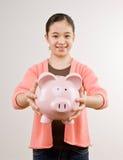 Het hoogtepunt van het de holdingsspaarvarken van het meisje van besparingen Stock Afbeeldingen