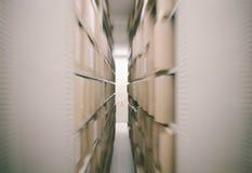 Het hoogtepunt van metaalplanken van documenten in een oud archief worden opgeslagen dat stock fotografie