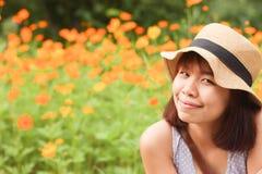 Het hoogtepunt van portretvrouwen van bloeiende oranje bloem Royalty-vrije Stock Afbeeldingen