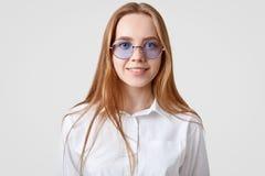 Het horizontale portret van vrolijke vrouwelijke student draagt wit overhemd, in ronde schaduwen, bekijkt direct camera, modellee stock foto