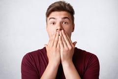 Het horizontale schot van bedwelmd sterk mannetje behandelt mond met handen, kijkt in surprisement, unexecpected recives nieuws v royalty-vrije stock afbeelding