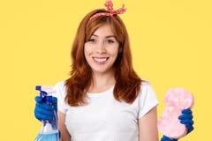 Het horizontale schot van gelukkige huisvrouw draagt toevallige t-shirt en de redy hoofdband, om huis schoon te maken, houdt neve royalty-vrije stock foto