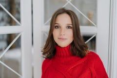 Het horizontale schot van kalme mooie jonge Europese vrouw draagt warme rode sweater, heeft omhooggaand maken en de gezonde zacht stock foto