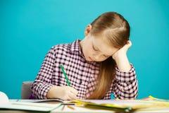 Het horizontale schot van meisje bij bureau schrijft zorgvuldig in notitieboekjetaak, zittend over blauw geïsoleerde achtergrond  stock fotografie