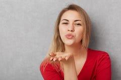 Het horizontale schot van mooie jonge vrouw met aantrekkelijke verschijning, maakt luchtkus, blaast bij camera, draagt rode sweat royalty-vrije stock fotografie