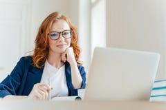 Het horizontale schot van prettige kijkende succesvolle professionele vrouwelijke advocaat leert cliëntengeval, werkt aan moderne royalty-vrije stock foto