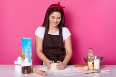Het horizontale schot van vrolijke huisvrouw kneedt deeg voor het maken van pizza, gebruikt verschillende ingrediëntenbloem, egss stock fotografie