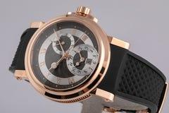 Het horloge van mensen met zwarte rubber met de wijzers van de klok mee riem, in gouden lichaam, zwarte wijzerplaat, zilver, chro stock foto